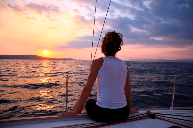 Passeio romântico de barco ao por do sol. Rapariga a ver o sunset